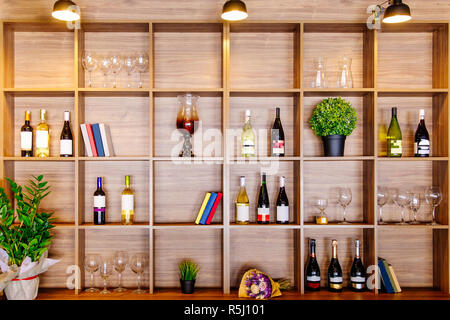 Bottles of white and red wine on a wooden shelf with books in private winery cabinet room interior - Stock Photo