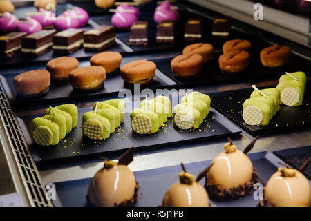 Delicious cakes of different flavors and colors on display in a confectionery shop - Stock Photo
