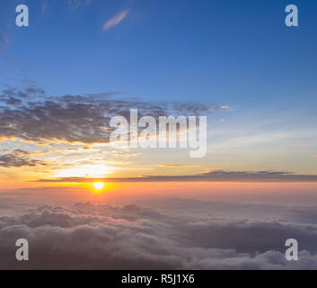 Rising sun in the early morning over sea of mist - Stock Photo