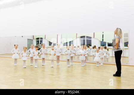Moscow, Russia, 09.06.2018: Group of girl kids doing fitness exercises in gym together - gymnastic, stretching, yoga and kids sport concept - Stock Photo