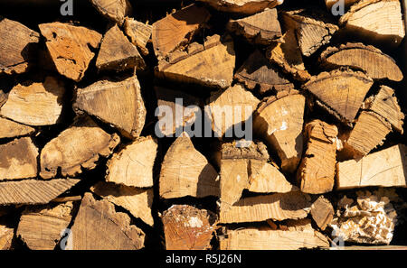 Big pieces of dried cured firewood piled high ready to burn - Stock Photo
