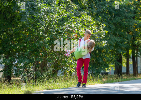 Happy laughing children playing and having fun in the park. Outdoors portrait on a sunny summer day. Older brother walking with younger sister in the park - Stock Photo