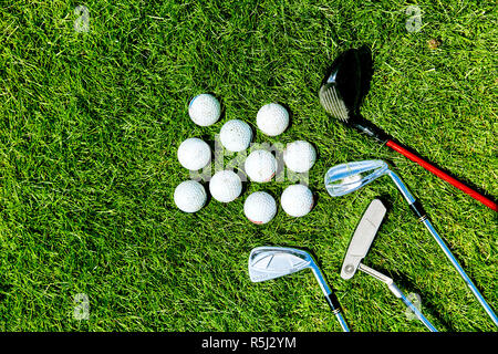 golf clubs and balls on grass background for text - Stock Photo