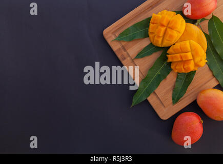 Mango fruit and mango cubes on the wooden cutting board. Tropical fruit concept with a huge amount of negative space for text. - Stock Photo