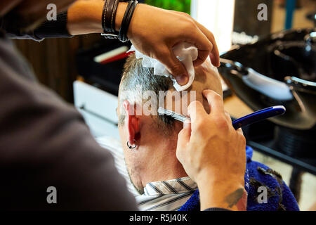 Portrait of young bald bearded man getting shaved with straight edge razor by hairdresser at barbershop on a wooden texture. - Stock Photo