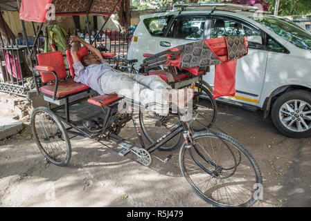 Rickshaw man sleeping in his rickshaw, Jaipur, Rajasthan, India - Stock Photo