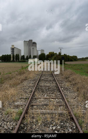 Old train rails in Polisot Aube Champagne France with grain elevator - Stock Photo