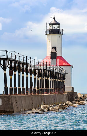 An elevated catwalk leads to the historic East Pierhead Lighthouse on Lake Michigan at Michigan City, Indiana. - Stock Photo