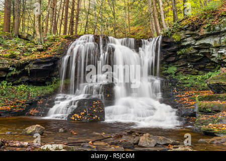 A beautiful cascading waterfall is surrounded by fall foliage on Dry Run in Pennsylvania's Loyalsock State Forest. - Stock Photo