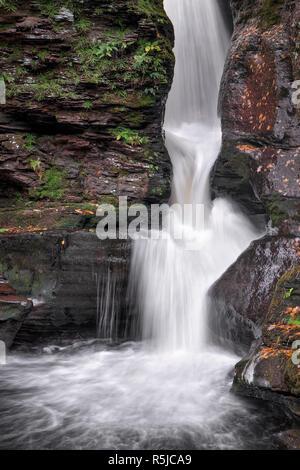 Adams Falls, one of many beautiful waterfalls in Pennsylvania's Ricketts Glen State Park, splashes through a rocky ravine. - Stock Photo