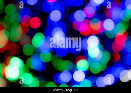Christmas and festive multicoloured lights, blurred to give an abstract effect and colourful Christmas background. - Stock Photo