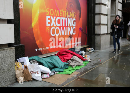 Regents Street, London, UK1st Dec, 2018. A homeless person and belongings asleep, as people walk by and do their Christmas shopping. Penelope Barritt/Alamy Live News - Stock Photo