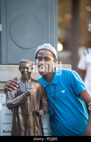 Johannesburg, South Africa, 1st December 2018. A man enjoys taking a selfie with a miniature Nelson Mandela statue, next to the larger one, in Nelson Mandela Square in Sandton. South Africa is currently celebrating the centenary of Madiba's birth. Credit: Eva-Lotta Jansson/Alamy Live News - Stock Photo