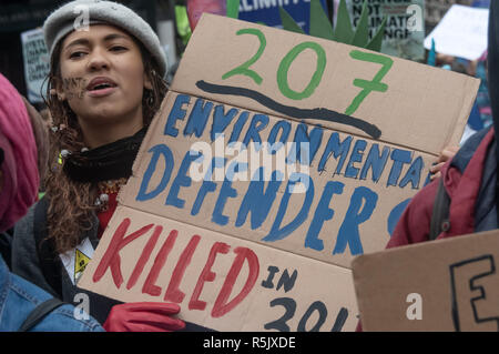 London, UK. 1st December 2018. A woman holds a poster '207 envionmental defenders killed in 2017'. Several thousand marched through London from a Campaign against Climate Change led rally outside the Polish Embassy where grave doubts were expressed about next week's UN climate talks in Katowice, Poland, which are being sponsored by leading firms in Poland's fossil fuel industry.  - Stock Photo