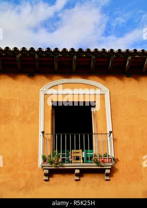 A large open window with yellow and green wooden chairs - Stock Photo