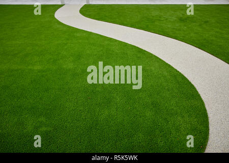 maintenance free artificial turf  lawn a modern synthetic grass carpet with resin path - Stock Photo