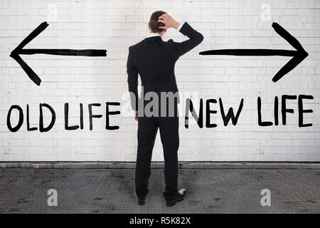 Confused Businessman Looking At Old And New Life On Wall - Stock Photo