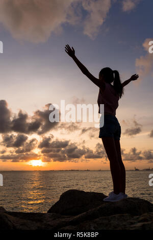 Silhouette of woman open hands up - Stock Photo