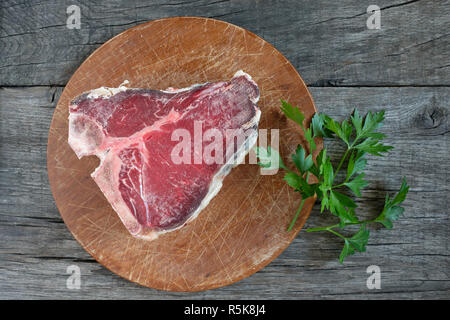 raw dry beef t-bone steak with parsley - Stock Photo