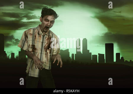 Horrible asian zombie man with blood standing - Stock Photo