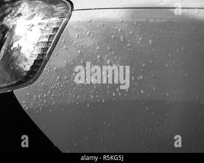CLOSE-UP OF RAINDROPS ON CAR BODY - Stock Photo