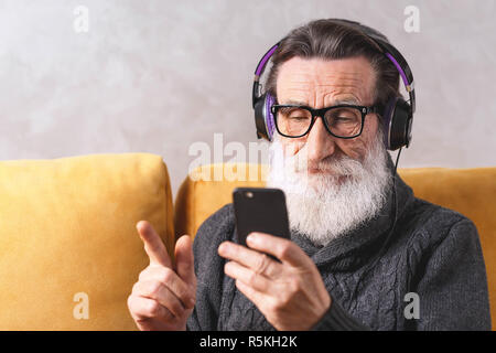 Senior contemporary bearded man in glasses wearing grey pullover learning to use the smartphone while sitting in headphones on a yellow sofa in his light living room, modern technology, communication concept - Stock Photo