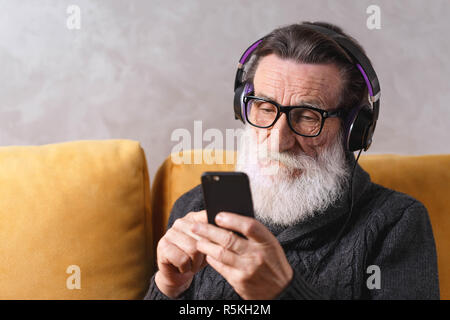 Senior contemporary bearded man in glasses wearing grey pullover writting message on the smartphone while sitting in headphones on a yellow sofa in his light living room, modern technology, communication concept - Stock Photo