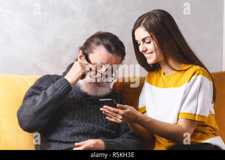 Senior handsome bearded man in glasses wearing grey pullover sitting with his adult long haired beautiful daughter on the yellow sofa and looking seriously on the smartphone, modern technology, communication concept - Stock Photo