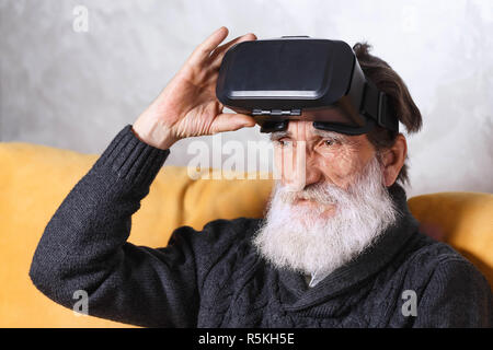 Contemporary senior bearded man in grey pullover sitting in VR goggles on the yellow sofa in the light living room, future technology concept - Stock Photo
