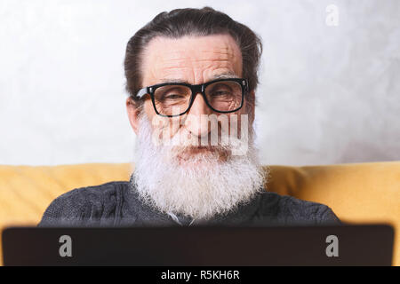 Cheerful senior bearded man in glasses and grey pullover chatting on Facebook on his laptop while sitting on the yellow sofa in the light living room, modern technology, communication concept