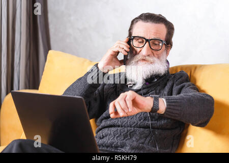 Contemporary senior bearded man in glasses and grey pullover chatting on the smartphone and watching time in his apple watch while sitting on the yellow sofa in the light living room, modern technology, communication concept - Stock Photo