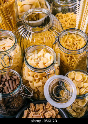 Different pasta in large jars - Stock Photo