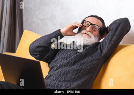 Contemporary senior bearded man in glasses and grey pullover relaxing and chatting on the smartphone with his friend while sitting on the yellow sofa in the light living room, modern technology, communication concept - Stock Photo