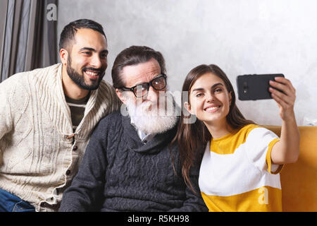 Brunette bearded son and brunette long haired daughter smiling and taking selfie with they senior bearded father in glasses while sitting on the yellow sofa in the light living room, modern technology, communication concept