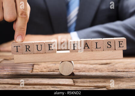 Businessman With True And False Blocks On Seesaw - Stock Photo