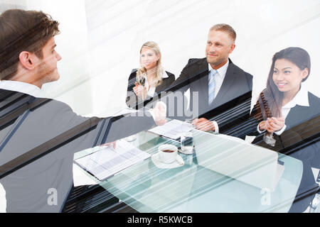 Partners Shaking Hands At Desk - Stock Photo