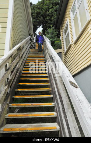 A woman descends a long and steep set of steps between two houses - Stock Photo