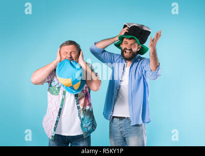 The two football fans singing the national anthem over blue - Stock Photo