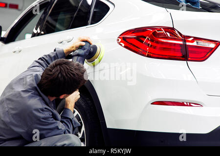 Car detailing - Hands with orbital polisher in auto repair shop - Stock Photo