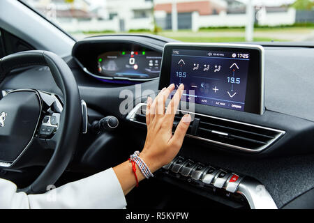 Moscow, Russia, 08.05.2018: Cropped rear view shot young woman in a car. One is driving, the other is using touch screen display to change the temperature. Play something else - Stock Photo
