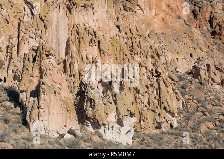 Unusual, colorful tufa rock formations and cliffs with a confusing pattern of eroded holes and small caves in Bandelier National Monument - Stock Photo