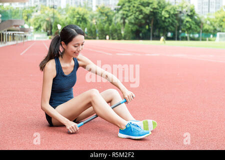 Woman using roller massage stick in sport stadium - Stock Photo