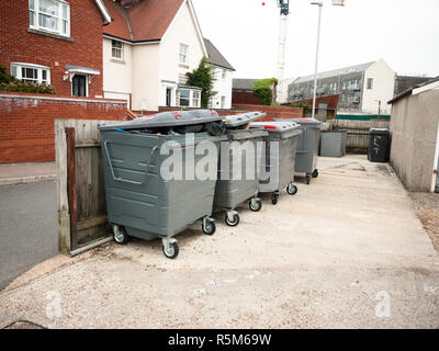 a row of black waste bins outside full - Stock Photo