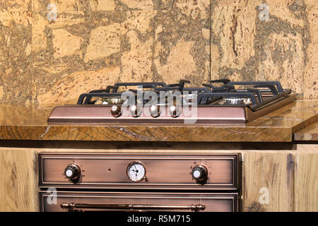 Retro style bronze color gas stove top on marble background - Stock Photo