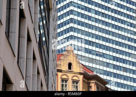 contrast between old building and new building - Stock Photo