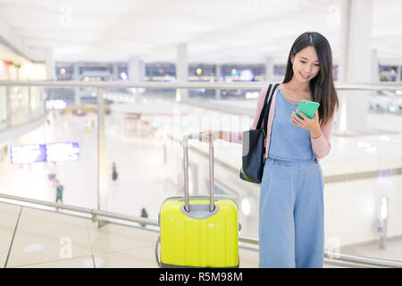 Woman use of smart phone in Hong Kong airport - Stock Photo