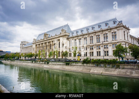 September 22, 2017 Bucharest/Romania - Palace of Justice in downtown Bucharest reflected in Dambovita River; dramatic cloudy sky in the background - Stock Photo