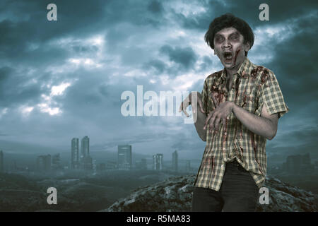 Scary asian zombie man with open mouth standing - Stock Photo