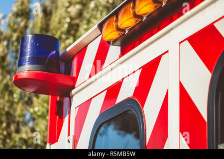 blue flashing light on a red ambulance - Stock Photo