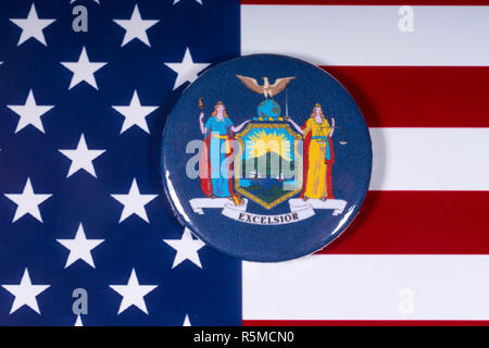 London, UK - November 15th 2018: The symbol or seal of the state of New York, pictured over the flag of the United States of America. - Stock Photo